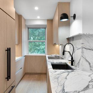 ニューヨークのコンテンポラリースタイルのおしゃれなキッチン (アンダーカウンターシンク、フラットパネル扉のキャビネット、中間色木目調キャビネット、クオーツストーンカウンター、マルチカラーのキッチンパネル、クオーツストーンのキッチンパネル、パネルと同色の調理設備、無垢フローリング、茶色い床、マルチカラーのキッチンカウンター) の写真
