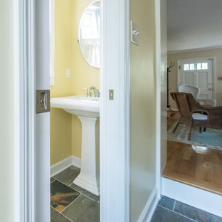This is an example of a cloakroom in Richmond with a two-piece toilet, yellow walls, slate flooring, a pedestal sink and grey floors.