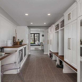 Inredning av ett klassiskt stort beige parallellt beige grovkök, med en undermonterad diskho, luckor med infälld panel, vita skåp, bänkskiva i kvarts, grå väggar, klinkergolv i porslin, en tvättmaskin och torktumlare bredvid varandra, beiget golv, vitt stänkskydd och stänkskydd i trä