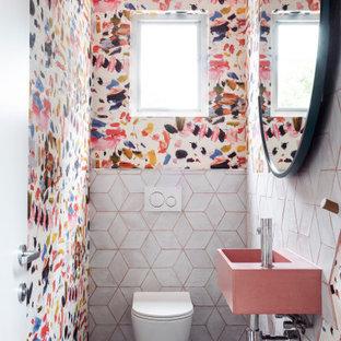 Immagine di un piccolo bagno di servizio minimal con WC monopezzo, piastrelle bianche, piastrelle in gres porcellanato, pareti multicolore, pavimento in cemento, lavabo sospeso, top in cemento, pavimento nero, top rosa, mobile bagno sospeso e carta da parati