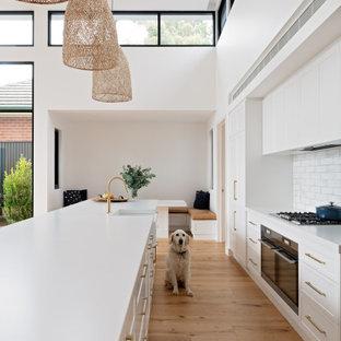 Inspiration för mellanstora moderna vitt kök, med en rustik diskho, skåp i shakerstil, vita skåp, bänkskiva i kvarts, vitt stänkskydd, stänkskydd i keramik, rostfria vitvaror, mellanmörkt trägolv, en köksö och brunt golv