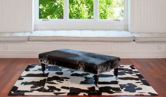 Grey speckle cowhide ottoman with wood legs & chrome wheels