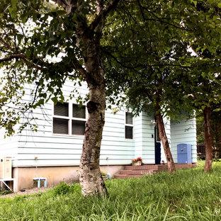 Imagen de puerta principal de estilo de casa de campo, grande, con paredes azules, suelo de baldosas de porcelana, puerta simple, puerta azul y suelo rosa