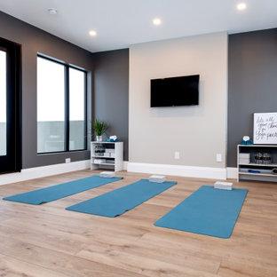 Foto di un ampio studio yoga design con pareti grigie, pavimento in legno massello medio e pavimento marrone