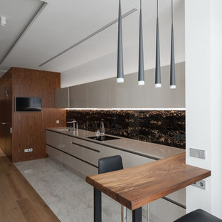 This is an example of a contemporary single-wall kitchen in Moscow with flat-panel cabinets, beige cabinets, black splashback, marble floors, a peninsula, white floor and beige benchtop.