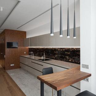 Неиссякаемый источник вдохновения для домашнего уюта: линейная кухня в современном стиле с плоскими фасадами, бежевыми фасадами, черным фартуком, мраморным полом, полуостровом, белым полом и бежевой столешницей