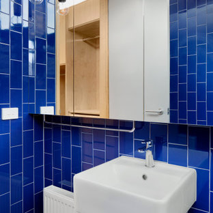 Inspiration for a small contemporary master bathroom in Melbourne with an open shower, blue tile, ceramic tile, blue walls, ceramic floors, a wall-mount sink, grey floor, an open shower, a single vanity and a floating vanity.