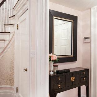 Aménagement d'un grand hall d'entrée romantique avec un mur rose, un sol en bois foncé et une porte simple.
