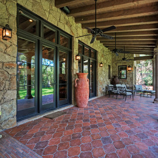 Example of a tuscan patio design in Austin with a roof extension