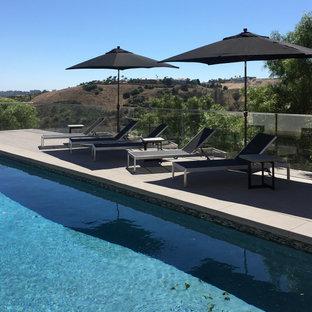 Immagine di un'ampia piscina stile marinaro rettangolare dietro casa con pedane