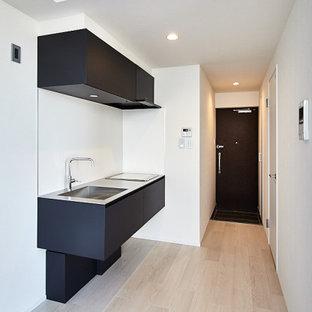 東京23区の小さいコンテンポラリースタイルのおしゃれなキッチン (合板フローリング、ベージュの床、クロスの天井、一体型シンク、インセット扉のキャビネット、黒いキャビネット、ステンレスカウンター、白いキッチンパネル、ガラス板のキッチンパネル、黒い調理設備) の写真