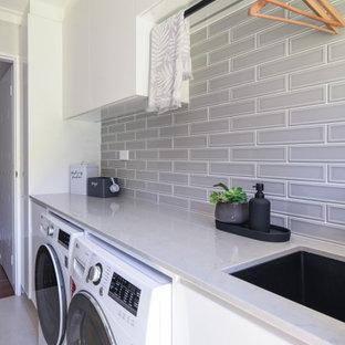 Idéer för en mellanstor modern grå linjär tvättstuga enbart för tvätt, med en undermonterad diskho, släta luckor, vita skåp, bänkskiva i kvarts, grått stänkskydd, stänkskydd i keramik, vita väggar, klinkergolv i keramik, en tvättmaskin och torktumlare bredvid varandra och beiget golv