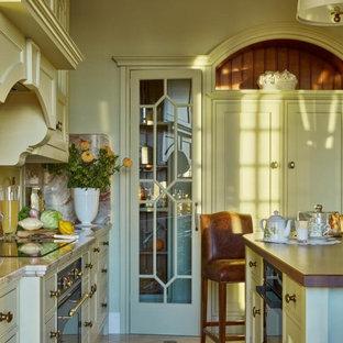 モスクワの広いトラディショナルスタイルのおしゃれなキッチン (アンダーカウンターシンク、ガラス扉のキャビネット、緑のキャビネット、大理石カウンター、マルチカラーのキッチンパネル、御影石のキッチンパネル、パネルと同色の調理設備、大理石の床、ベージュの床) の写真