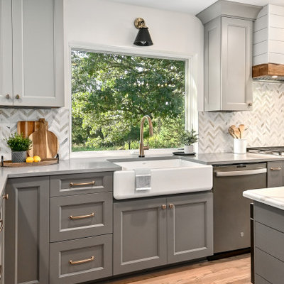 Eat-in kitchen - huge cottage l-shaped medium tone wood floor and brown floor eat-in kitchen idea in Milwaukee with a farmhouse sink, shaker cabinets, gray cabinets, quartz countertops, white backsplash, marble backsplash, stainless steel appliances, an island and gray countertops