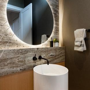 Idéer för mellanstora funkis beige toaletter, med släta luckor, skåp i ljust trä, en vägghängd toalettstol, grå kakel, marmorkakel, ett piedestal handfat och bänkskiva i travertin