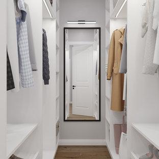 Ejemplo de armario vestidor unisex, escandinavo, pequeño, con armarios abiertos, puertas de armario blancas, suelo marrón y suelo de madera en tonos medios