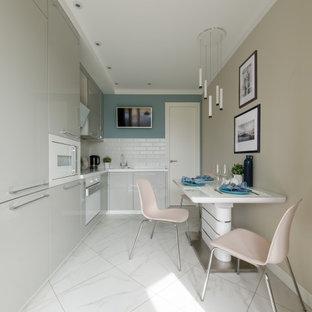 Идея дизайна: маленькая, узкая отдельная, угловая кухня в современном стиле с врезной раковиной, плоскими фасадами, серыми фасадами, столешницей из акрилового камня, белым фартуком, фартуком из керамической плитки, белой техникой, полом из керамогранита, белым полом и белой столешницей