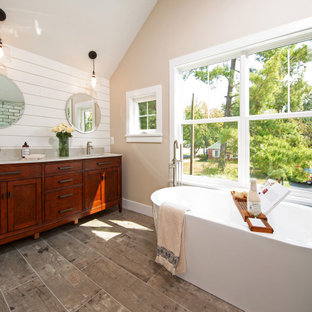 Photo of a transitional master bathroom with shaker cabinets, medium wood cabinets, a freestanding tub, an alcove shower, white tile, beige walls, wood-look tile, an undermount sink, engineered quartz benchtops, brown floor, a sliding shower screen, beige benchtops, a double vanity, a built-in vanity, vaulted and planked wall panelling.