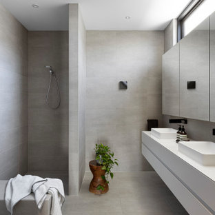 Design ideas for a large modern master bathroom in Melbourne with flat-panel cabinets, white cabinets, an open shower, gray tile, ceramic tile, ceramic floors, engineered quartz benchtops, grey floor, an open shower, white benchtops, a shower seat, a double vanity and a floating vanity.