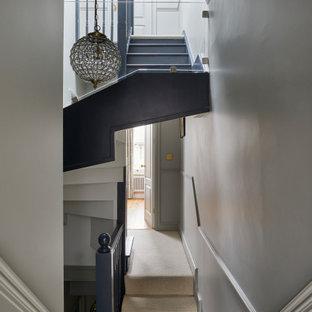 Kleine Klassische Treppe mit Teppich-Setzstufen, Holzgeländer und Holzdielenwänden in London