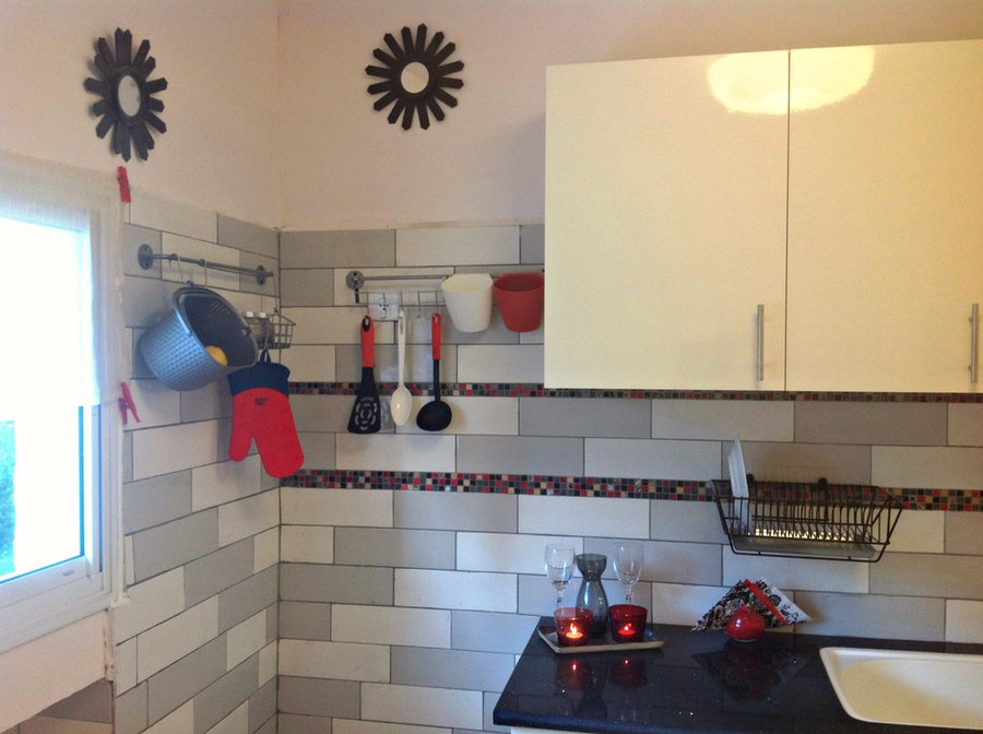 subway tiles in gray and white with blk/red mosaic strip