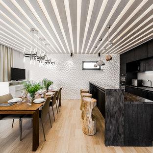 Неиссякаемый источник вдохновения для домашнего уюта: линейная кухня в современном стиле с монолитной раковиной, плоскими фасадами, черными фасадами, белым фартуком, техникой из нержавеющей стали и светлым паркетным полом