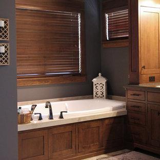 Modelo de cuarto de baño principal, de estilo americano, grande, con lavabo bajoencimera, armarios con paneles empotrados, puertas de armario de madera oscura, encimera de acrílico, bañera encastrada, ducha abierta, sanitario de dos piezas, baldosas y/o azulejos de porcelana, paredes grises y suelo de baldosas de porcelana