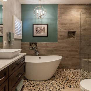 Свежая идея для дизайна: большая главная ванная комната в стиле неоклассика (современная классика) с фасадами с утопленной филенкой, темными деревянными фасадами, отдельно стоящей ванной, открытым душем, раздельным унитазом, коричневой плиткой, плиткой под дерево, бежевыми стенами, настольной раковиной, мраморной столешницей, бежевым полом, открытым душем, белой столешницей, тумбой под две раковины и встроенной тумбой - отличное фото интерьера