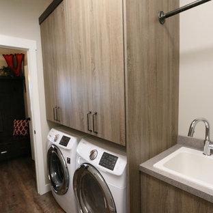 Mittelgroße Industrial Waschküche in L-Form mit Einbauwaschbecken, flächenbündigen Schrankfronten, hellbraunen Holzschränken, Laminat-Arbeitsplatte, grauer Wandfarbe, Vinylboden und Waschmaschine und Trockner nebeneinander in Sonstige