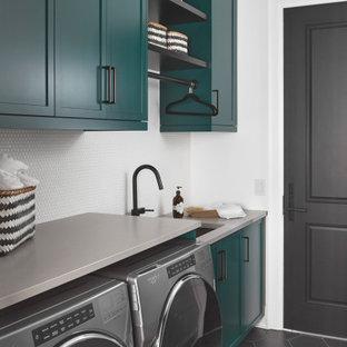 Modern inredning av en mellanstor grå linjär grått tvättstuga enbart för tvätt, med en undermonterad diskho, skåp i shakerstil, gröna skåp, bänkskiva i kvarts, vitt stänkskydd, stänkskydd i keramik, vita väggar, klinkergolv i porslin, en tvättmaskin och torktumlare bredvid varandra och svart golv