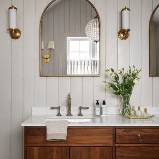 Lantlig inredning av ett stort grå grått en-suite badrum, med släta luckor, skåp i mellenmörkt trä, ett fristående badkar, en toalettstol med separat cisternkåpa, grå väggar, marmorgolv, ett undermonterad handfat, marmorbänkskiva, grått golv och dusch med gångjärnsdörr