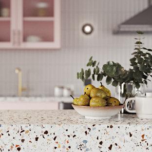 Diseño de cocina comedor lineal, minimalista, con fregadero bajoencimera, armarios tipo vitrina, encimera de terrazo, salpicadero blanco, salpicadero de azulejos de cerámica, electrodomésticos de acero inoxidable, suelo de madera clara y una isla