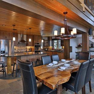 バンクーバーのラスティックスタイルのおしゃれなLDK (白い壁、スレートの床、コーナー設置型暖炉、積石の暖炉まわり、グレーの床、板張り天井) の写真