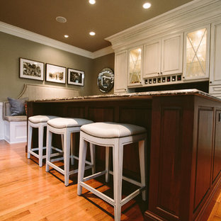 Inspiration for a medium sized traditional single-wall wet bar in Baltimore with a submerged sink, raised-panel cabinets, white cabinets, engineered stone countertops, grey splashback, stone tiled splashback, medium hardwood flooring and brown floors.