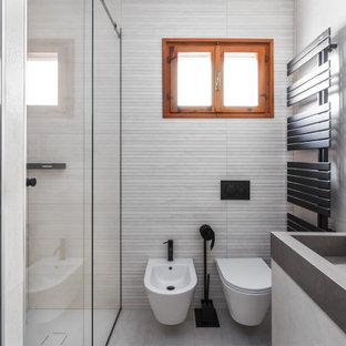 Idee per una piccola stanza da bagno minimal con ante a filo, ante grigie, WC sospeso, piastrelle beige, piastrelle in ceramica, pareti beige, pavimento in gres porcellanato, lavabo integrato, top piastrellato, pavimento beige, top grigio e mobile bagno sospeso