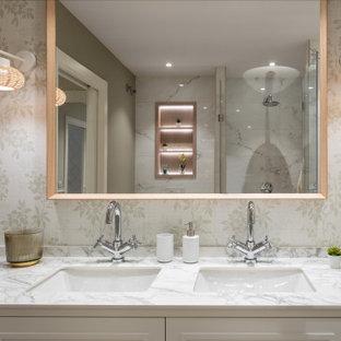 Идея дизайна: большая главная ванная комната в стиле неоклассика (современная классика) с фасадами с декоративным кантом, белыми фасадами, душем без бортиков, инсталляцией, белой плиткой, керамической плиткой, зелеными стенами, полом из ламината, врезной раковиной, столешницей из искусственного кварца, бежевым полом, душем с распашными дверями, белой столешницей, нишей, встроенной тумбой, обоями на стенах и тумбой под две раковины