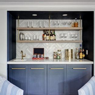 ニューヨークの中くらいのビーチスタイルのおしゃれなウェット バー (I型、アンダーカウンターシンク、シェーカースタイル扉のキャビネット、青いキャビネット、クオーツストーンカウンター、グレーのキッチンパネル、磁器タイルのキッチンパネル、淡色無垢フローリング、茶色い床、白いキッチンカウンター) の写真