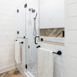 Inspiration for a mid-sized country master bathroom in Milwaukee with shaker cabinets, white cabinets, an alcove shower, white tile, subway tile, white walls, painted wood floors, an undermount sink, engineered quartz benchtops, brown floor, a hinged shower door, grey benchtops, a niche, a double vanity, a built-in vanity and planked wall panelling.