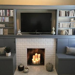 Modelo de sala de estar abierta, contemporánea, pequeña, con paredes beige, suelo de baldosas de porcelana, chimenea tradicional, marco de chimenea de baldosas y/o azulejos, pared multimedia y suelo blanco