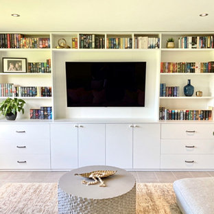 Design ideas for a mid-sized shabby-chic style enclosed home theatre in Brisbane with grey walls, porcelain floors, a wall-mounted tv and grey floor.