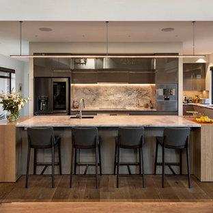 オークランドの広いコンテンポラリースタイルのおしゃれなキッチン (アンダーカウンターシンク、落し込みパネル扉のキャビネット、グレーのキャビネット、御影石カウンター、グレーのキッチンパネル、御影石のキッチンパネル、シルバーの調理設備、無垢フローリング、茶色い床、白いキッチンカウンター) の写真
