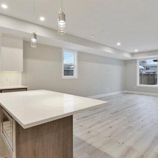 Inspiration för ett litet funkis allrum med öppen planlösning, med grå väggar, laminatgolv, en väggmonterad TV och grått golv