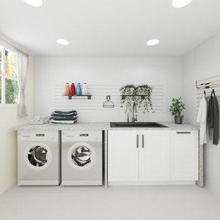 Klassisk inredning av en stor grå linjär grått tvättstuga enbart för tvätt, med en nedsänkt diskho, luckor med infälld panel, vita skåp, vita väggar, en tvättmaskin och torktumlare bredvid varandra och vitt stänkskydd