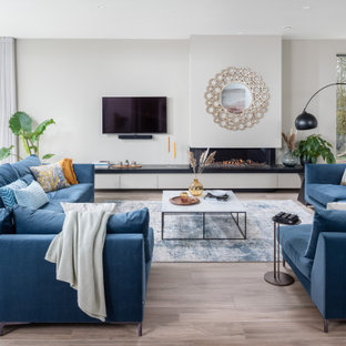 Medium sized beach style open plan games room in Dorset with white walls, light hardwood flooring, a ribbon fireplace, a freestanding tv and grey floors.