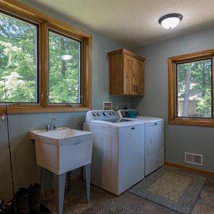 На фото: большая линейная универсальная комната в стиле рустика с хозяйственной раковиной, фасадами в стиле шейкер, светлыми деревянными фасадами, синими стенами, полом из винила, со стиральной и сушильной машиной рядом и разноцветным полом с