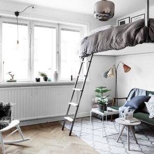 This is an example of a mid-sized scandinavian loft-style bedroom in Stockholm with white walls and light hardwood floors.