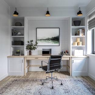 Пример оригинального дизайна: кабинет среднего размера с белыми стенами, полом из ламината, отдельно стоящим рабочим столом и коричневым полом