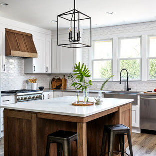 Example of a mid-sized transitional u-shaped medium tone wood floor and brown floor eat-in kitchen design in DC Metro with stainless steel appliances, an island, a farmhouse sink, shaker cabinets, white cabinets, quartz countertops, white backsplash and gray countertops