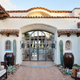 Idéer för en mycket stor amerikansk ingång och ytterdörr, med vita väggar, klinkergolv i keramik, en dubbeldörr, glasdörr och orange golv
