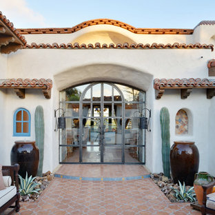 Entryway - huge southwestern ceramic floor and orange floor entryway idea in San Diego with white walls and a glass front door